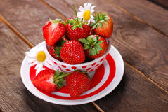 Bowl of fresh strawberries on wooden table Stock Photos