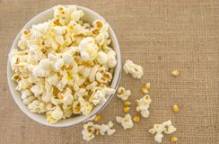 A bowl of freshly popped homemade popcorn. Fresh, delicious hand-popping popcorn in a bowl on a rustic jute base Royalty Free Stock Photo
