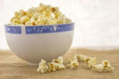 A bowl of freshly popped homemade popcorn. Fresh, delicious hand-popping popcorn in a bowl on a rustic jute base Stock Images