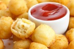 Bowl of fried small potato balls on white. Pot of ketchup Royalty Free Stock Photos