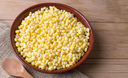 Bowl of frozen corn with a wooden spoon Royalty Free Stock Photos