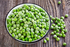 Bowl of frozen green peas Stock Images