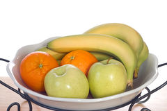 Bowl of Fruit. A white glass bowl full of bananas, oranges and apples, shot on a wooden board Stock Images