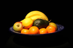 Bowl of Fruit. A bowl of fruit on a black background Stock Image