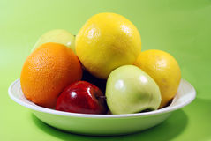 Bowl of fruit. Close up of bowl of assorted ripe fruits, isolated on green background Royalty Free Stock Images