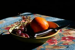 Bowl of fruit. With paring knife, dark, moody lighting royalty free stock image