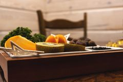 Bowl with fruit on the table, in the background a wooden wall and a chair. stock photos