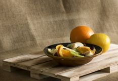 A bowl of fruit salad with an orange and a lemon. Still life representing a bowl of fruit salad composed of apple, kiwi, banana, orange and red cranberries stock photography
