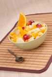 Bowl with fruit salad with piece of orange. And spoon Stock Images