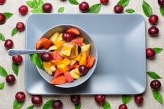 Bowl of fruit salad on rectangular plate. Stock Photos