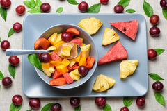 Bowl of fruit salad on rectangular plate. Royalty Free Stock Images