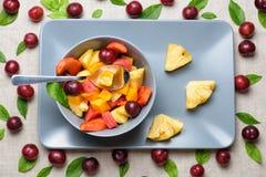 Bowl of fruit salad on rectangular plate. Stock Photo