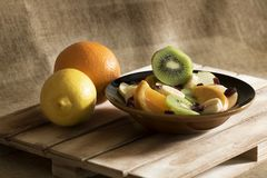 A bowl of fruit salad and some pieces of fresh fruit royalty free stock images
