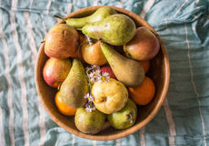 A bowl with fruit. A wooden bowl with apples, pears, flowers on blue pastel background Stock Image