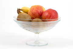 Bowl with fruits. Glass bowl with fruits and a white background Royalty Free Stock Image