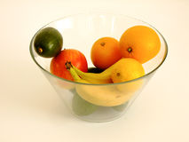 Bowl of Fruits. Glass Bowl with Bananas, Oranges, Apples, Lemon and Avocado in white Background Stock Image