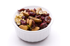 Bowl of fruits and nuts. Bowl of dried fruit and nuts isolated on white with a drop shadow Royalty Free Stock Images
