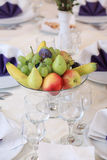 Bowl with fruits, on white elegant table Stock Photography