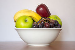 A bowl of fruits. A white bowl full of fruits with a white background Royalty Free Stock Images