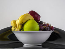 A bowl of fruits. A white bowl full of fruits with a white background stock photo