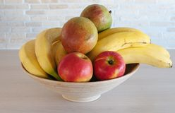 A bowl with fruits. A wooden bowl full of fruits royalty free stock image