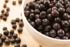 Bowl full of aronia spilled on wooden table Stock Photos