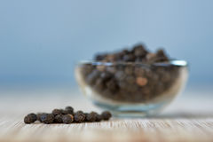 Bowl full of black pepper grains on a bamboo board Stock Photos