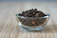 Bowl full of black pepper grains on a bamboo board Stock Photo
