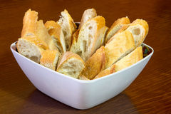 Bowl full of bread slices. Over a wooden background Royalty Free Stock Photo