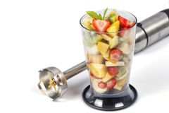 A bowl full of chopped fruit to prepare a smoothie next to the blender isolated. On white royalty free stock photo