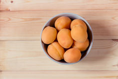 Bowl full of fresh apricots on wooden background. Top view. Stock Photo