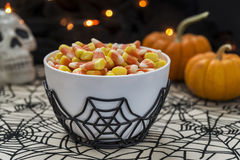 A bowl full of Halloween candy corn in a spooky setting. A bowl full of traditional candy corn in a spooky Halloween theme royalty free stock image