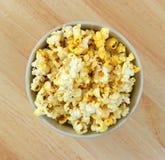 Bowl full of popcorn on tabletop Stock Photo