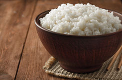 Bowl full of rice on wood Stock Photography