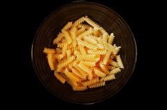 Bowl full of yellow fusilli pasta isolated on a black background. Shiny black bowl filled with uncooked yellow spirals of fusilli pasta isolated on a black royalty free stock photo
