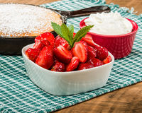Bowl of glazed strawberries with skillet cake Royalty Free Stock Image