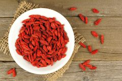 Bowl of goji berries over wood Royalty Free Stock Image