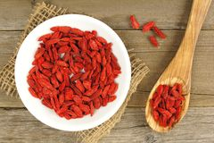 Bowl of goji berries with spoon over wood Royalty Free Stock Photography