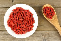 Bowl of goji berries with spoon over wood Royalty Free Stock Photos