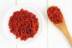Bowl of goji berries on white wood with spoon Royalty Free Stock Images