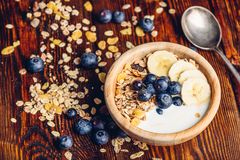 Bowl of Granola, Banana, Blueberry and Yoghurt. Bowl of Granola, Banana, Blueberry and Greek Yoghurt. Scattered Ingredients and Spoon on Wooden Table royalty free stock images
