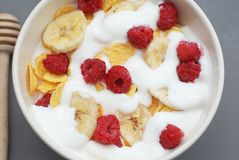 Bowl of Granola Cereals with Yogurt or Milk and Raspberries on Gray Background, Top view. stock photos