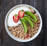 Bowl of granola with yogurt and fresh fruit. Healthy breakfast, bowl of granola with yogurt and fresh fruits on wooden table, top view Royalty Free Stock Photography