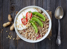 Bowl of granola with yogurt and fresh fruit. Healthy breakfast, bowl of granola with yogurt and fresh fruits on wooden table, top view Royalty Free Stock Photo