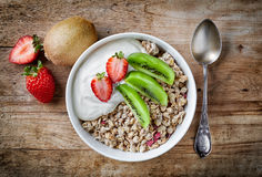 Bowl of granola with yogurt and fresh fruit. Healthy breakfast, bowl of granola with yogurt and fresh fruits on wooden table, top view Royalty Free Stock Images