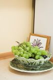 Bowl Of Grapes. Bunch of green grapes still attached to stems, in a green and white decorative bowl. Sitting in a kitchen area Royalty Free Stock Photos