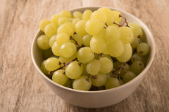 A bowl of grapes on an old wooden background. Royalty Free Stock Image