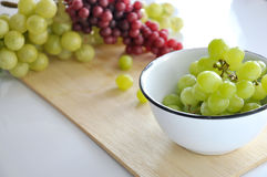Bowl of Grapes put on Wooden Board Royalty Free Stock Photo