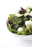 Bowl of Greek salad. Close up of bowl of appetizing Greek salad, isolated on white background Stock Photo