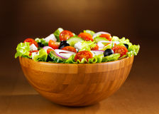 Bowl of greek salad. On wooden table Royalty Free Stock Photography